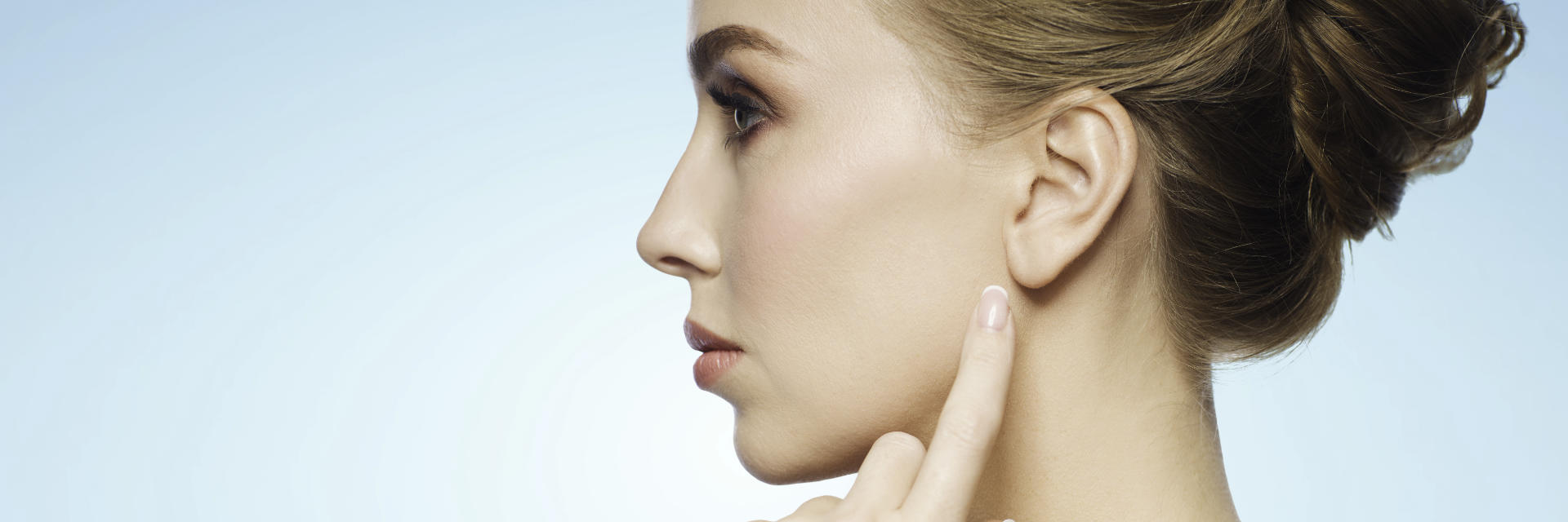 Profile of a young beautiful woman after ear surgery pointing at her left ear.