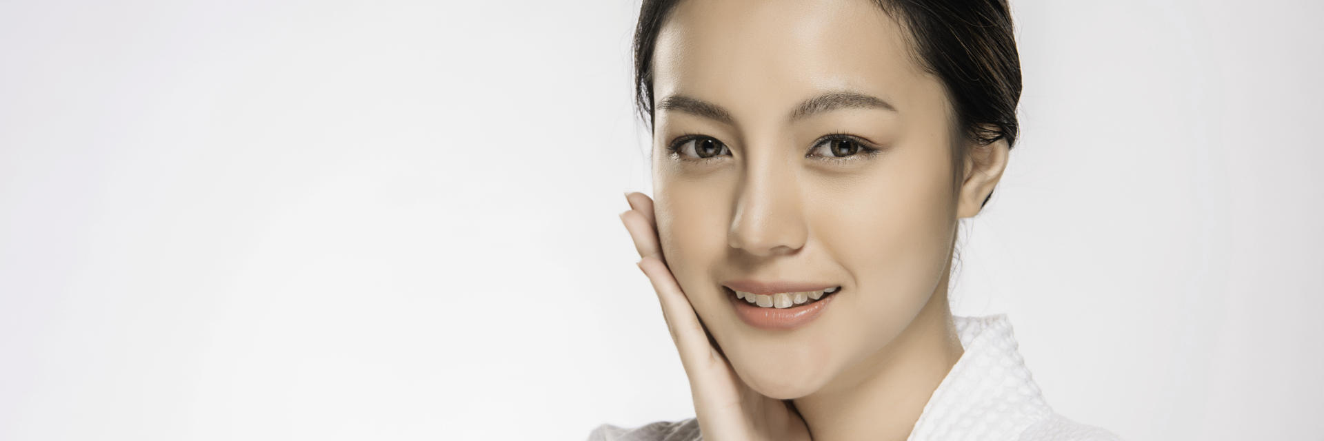 Beautiful face of a happy Asian woman after face cosmetic procedures touching her right cheek with her hand.