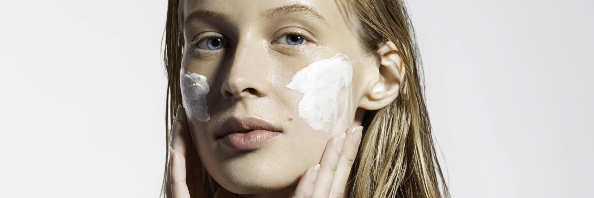 Young woman applying facial cream