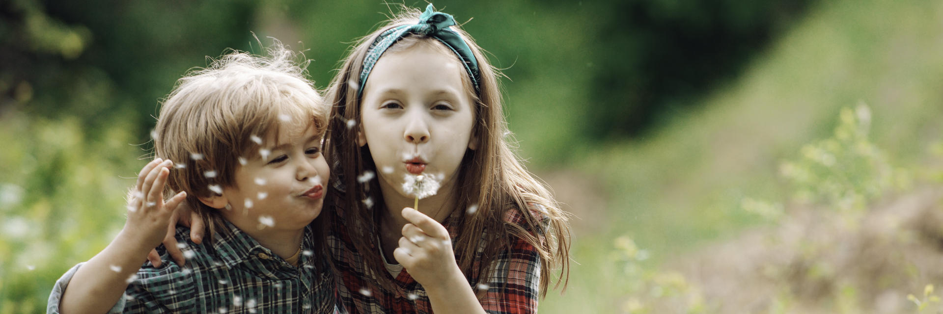 Little boy and girl blowing dandelion while playing in the garden